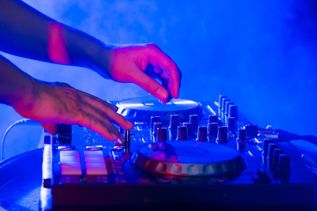 Dj hands on stage mixing, disc jockey and mix tracks on sound mixer controller, playing music at bar, disco tech or night club party. Premium Photo