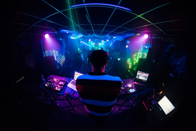Dj mixes music in a nightclub with people dancing Premium Photo