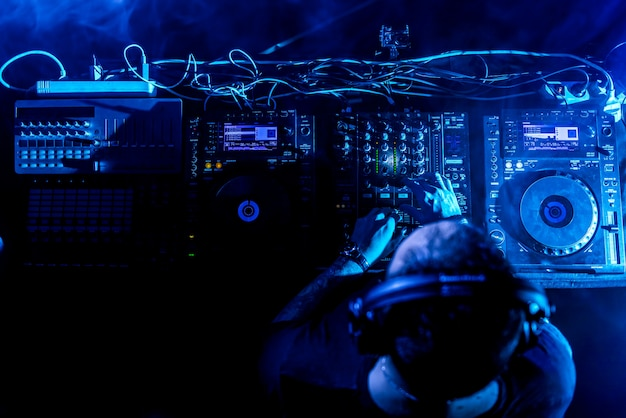 Dj playing house and techno music in a night club. mixing and controlling the music. Premium Photo