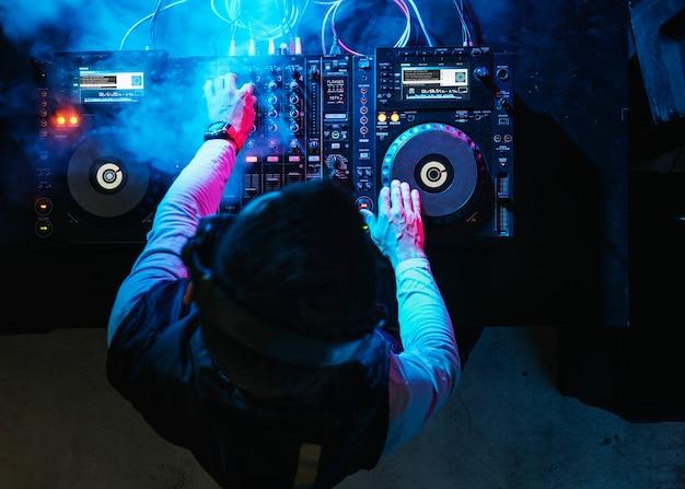 Dj playing music at sound mixer in night club Premium Photo