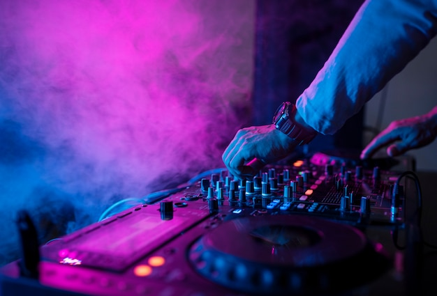 Dj playing music at sound mixer in night club Premium Photo