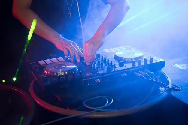 DJ playing turntable music on night club party Premium Photo