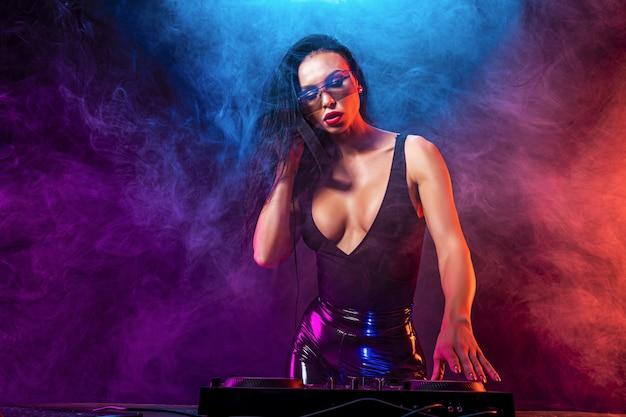 音楽を演奏するサングラスを持つ若いセクシーなdj Premium写真