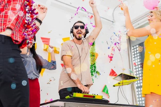 ターンテーブルのdj。白い部屋のパーティーで応援しながら紙吹雪を投げることを祝う若い人々のグループ。 Premium写真