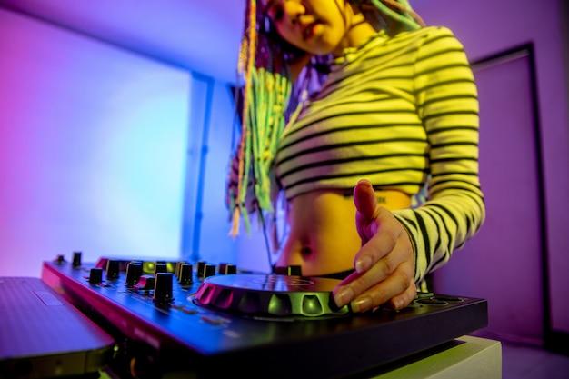 アジアの女の子djが夜のパーティーでターンテーブルを弾いているのはカラフルです。 Premium写真