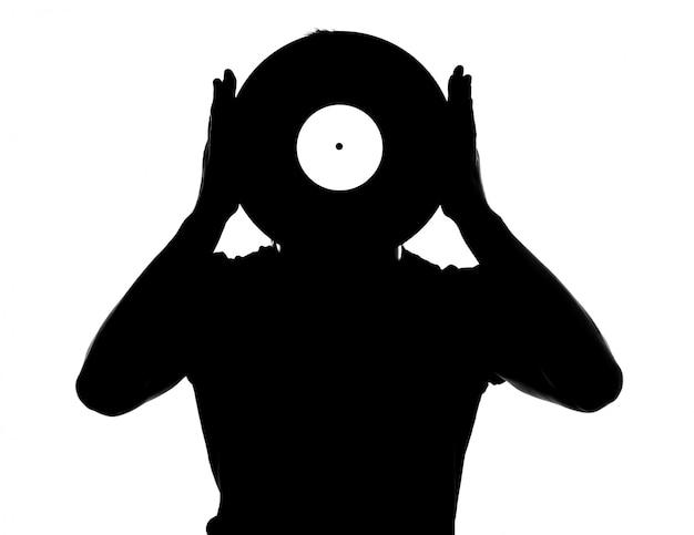 分離されたビニールレコードを持つ男性djのシルエット。 Premium写真