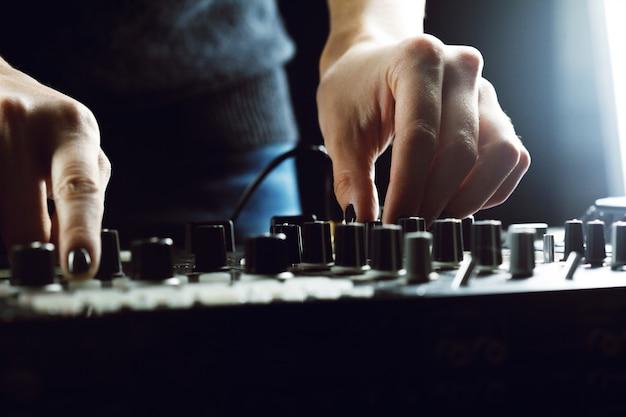 Djがミキサーのクローズアップで音楽を再生 Premium写真