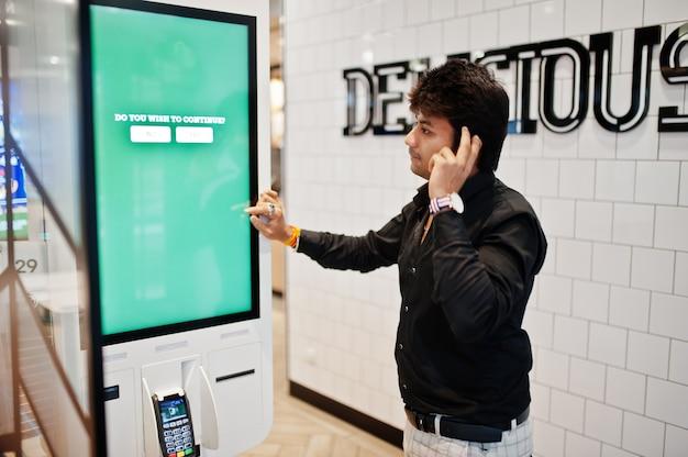 Вы хотите продолжить? индиец покупатель в магазине размещает заказы и оплачивает через киоск самооплаты за фастфуд, платежный терминал. его мысли о выборе. Premium Фотографии