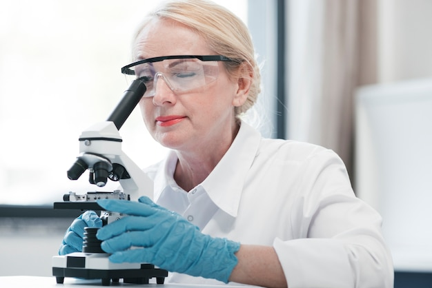 Doctor analyzing with a microscope Free Photo