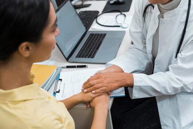 Врач и пациент, взявшись за руки после плохих новостей Бесплатные Фотографии