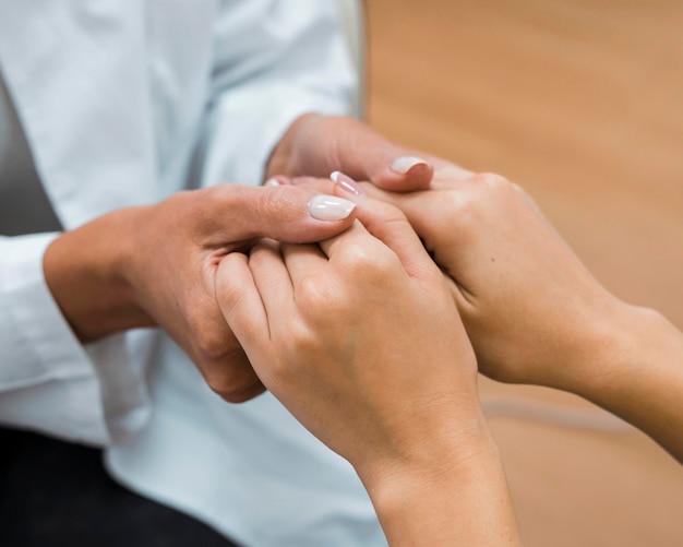 良いニュースのクローズアップの後に手をつないでいる医師と患者 無料写真
