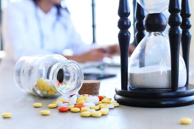 Врач в офисе с таблетками и песочными часами Бесплатные Фотографии