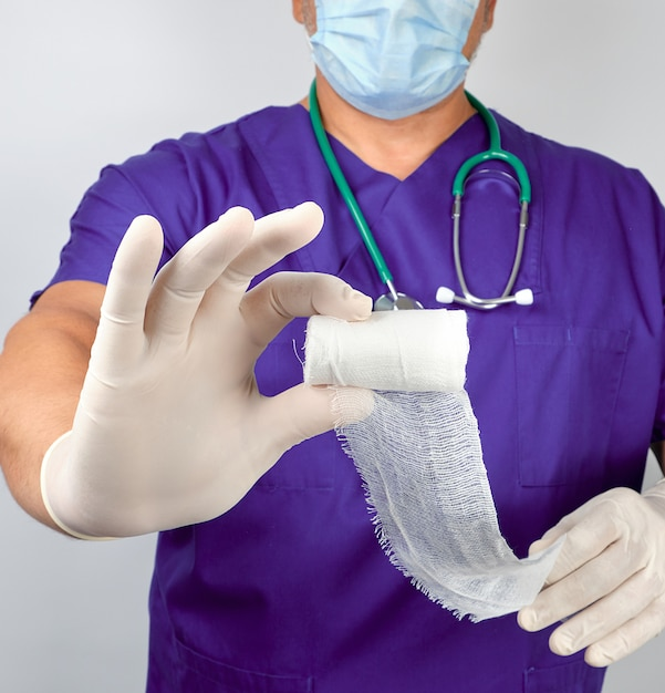 Doctor in blue uniform and latex gloves holding white sterile gauze dressing bandage Premium Photo