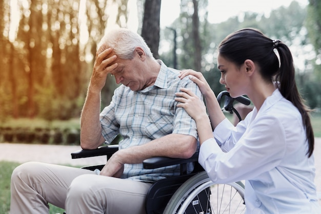 The doctor calms the dejected old man in a wheelchair Premium Photo