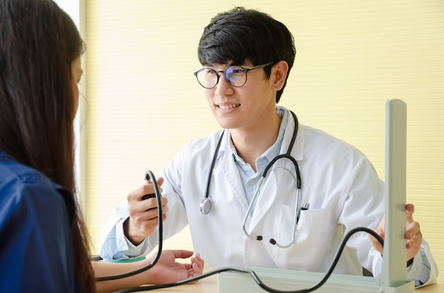 Doctor checking female patient blood pressure in medical office Premium Photo