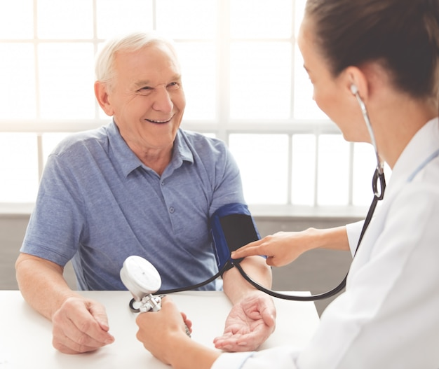 The doctor checks the pulse of an old patient in the clinic Premium Photo