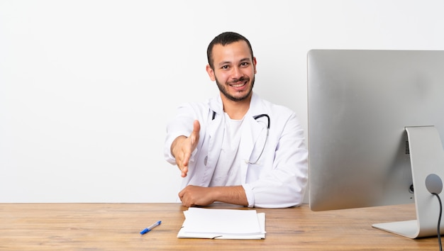 Doctor colombian man shaking hands for closing a good deal Premium Photo