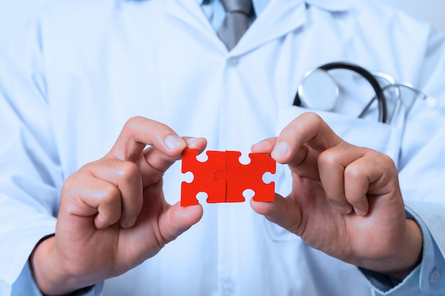 Doctor connecting jigsaw pieces of a head Premium Photo