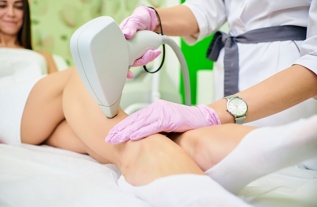 Doctor cosmetologist conducts the procedure of laser hair removal from the body of a girl Premium Photo