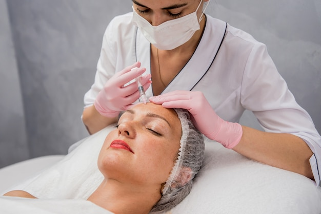 The doctor cosmetologist makes the facial injections procedure. young woman in a beauty salon. Premium Photo