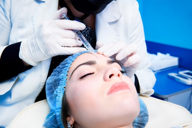 The doctor cosmetologist makes the rejuvenating facial injections procedure Premium Photo