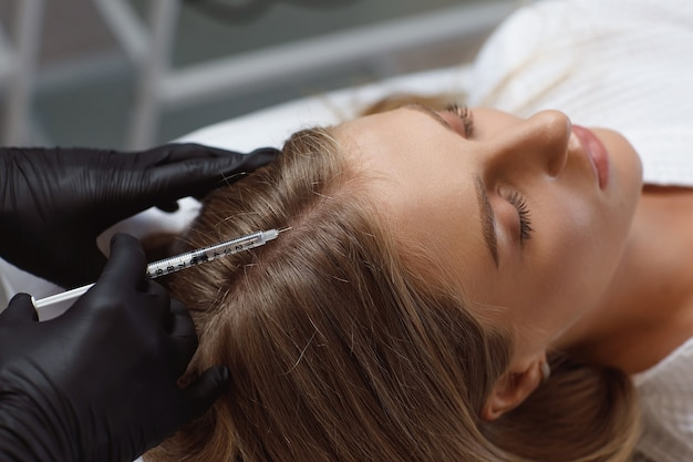 The doctor cosmetologist making mesotherapy injections in woman's head for stronger and healthier h