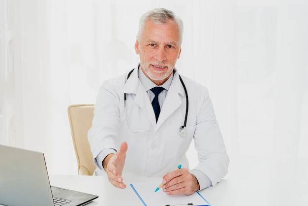 Doctor at desk holding out his hand Free Photo