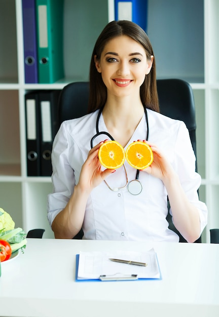 Doctor dietologist holds in the fresh orange hands. Premium Photo