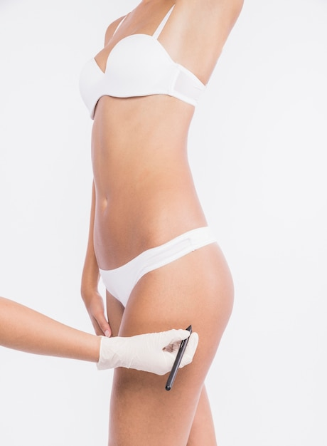 Doctor drawing lines on woman hip Free Photo