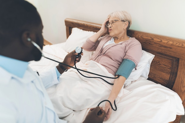 The doctor examines an elderly patient in a nursing home. Premium Photo