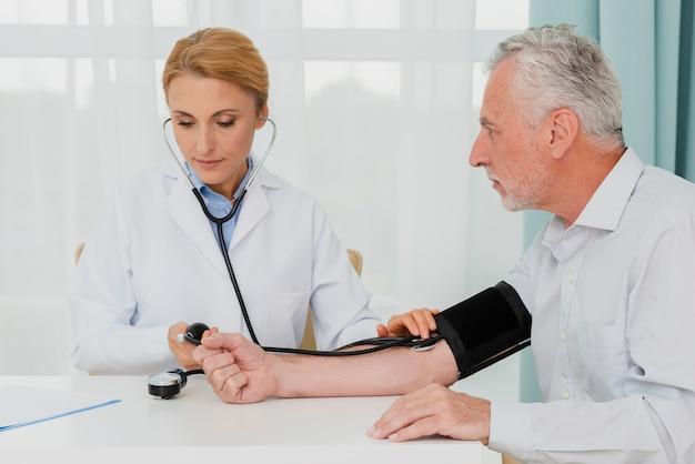 Doctor examining blood pressure Free Photo