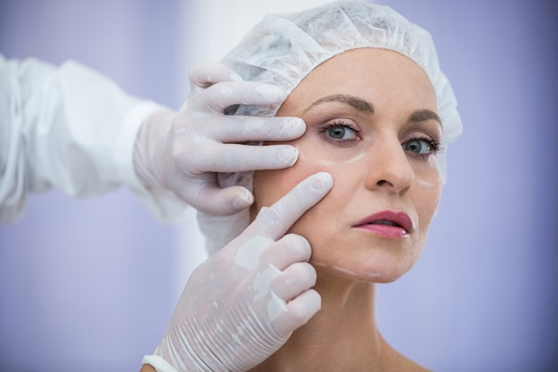 Doctor examining female patients face for cosmetic treatment Free Photo