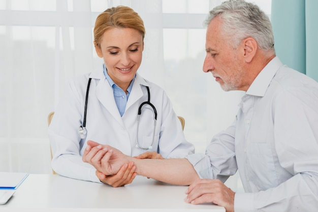Doctor examining hand of patient Free Photo