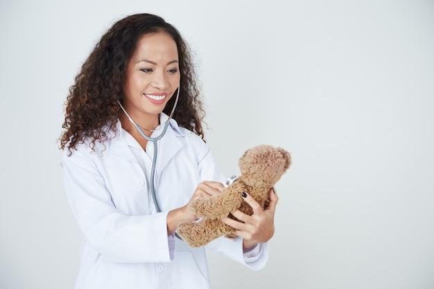 Doctor examining teddy bear Free Photo