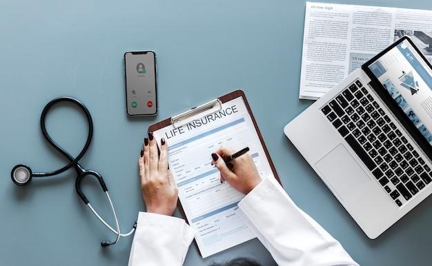 생명 보험 양식을 작성하는 의사 무료 사진