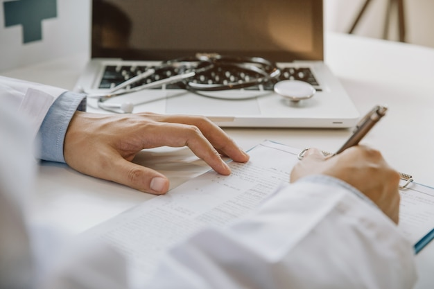 Doctor filling up medical form while sitting at the desk in hospital office. physician at work. Premium Photo