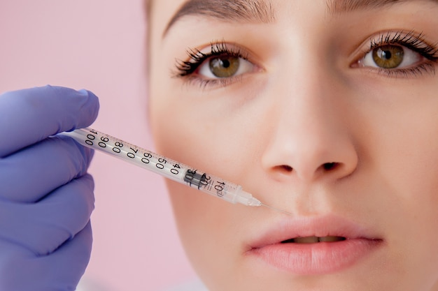 Premium Photo | Doctor in gloves giving woman botox injections in lips