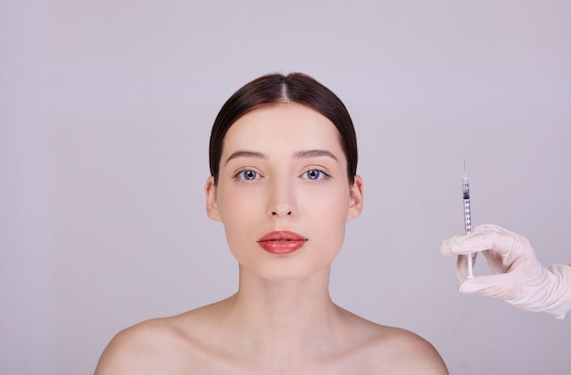 The doctor in gloves holds a syringe near the woman's face. Premium Photo