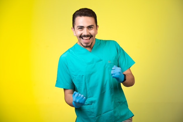 Doctor in green uniform and hand mask smiling and showing his happiness on yellow. Free Photo