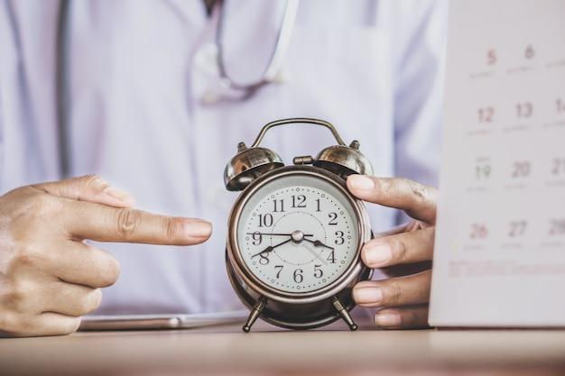 Доктор рука будильник показывает время Premium Фотографии