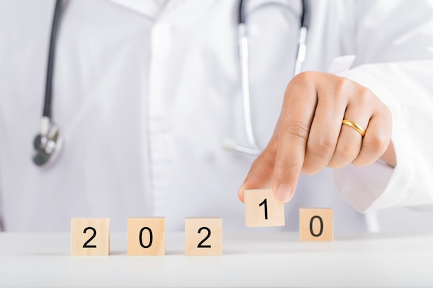 Doctor hand holding wooden blocks for 2021. new year and health concept. Premium Photo
