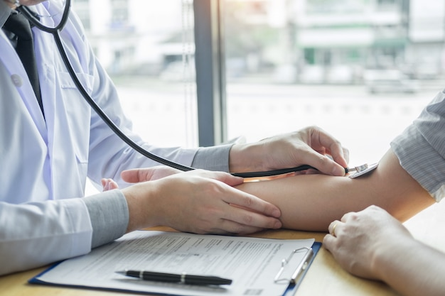 Doctor hands checking blood pressure of a patient Premium Photo