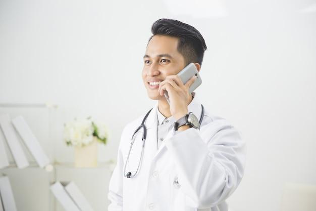 彼の診療所で電話を持つ医師 Premium写真