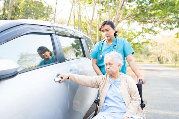 Врач помощи и ухода азиатская старшая женщина, чтобы получить ее автомобиль в парке. Premium Фотографии