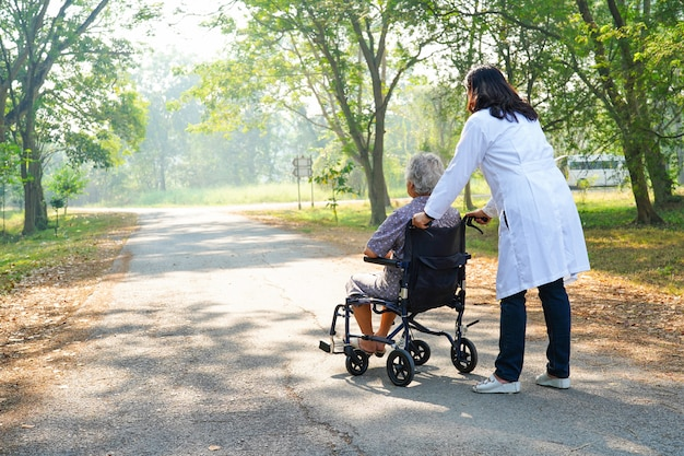 Doctor help and care asian senior or elderly old lady woman patient sitting on wheelchair Premium Photo