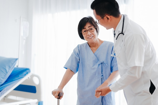 Doctor helping senior woman walking with a cane Premium Photo