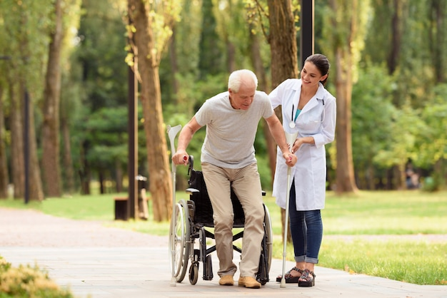 The doctor helps an aged patient to get on their feet Premium Photo