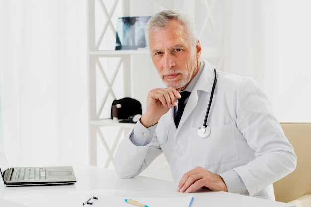 Doctor at his desk with hand on chin Free Photo