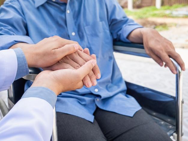 Doctor hold hand patient on wheelchair. Premium Photo