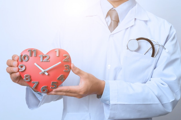 Доктор держит часы, концепция времени, медицинский и здравоохранение Premium Фотографии
